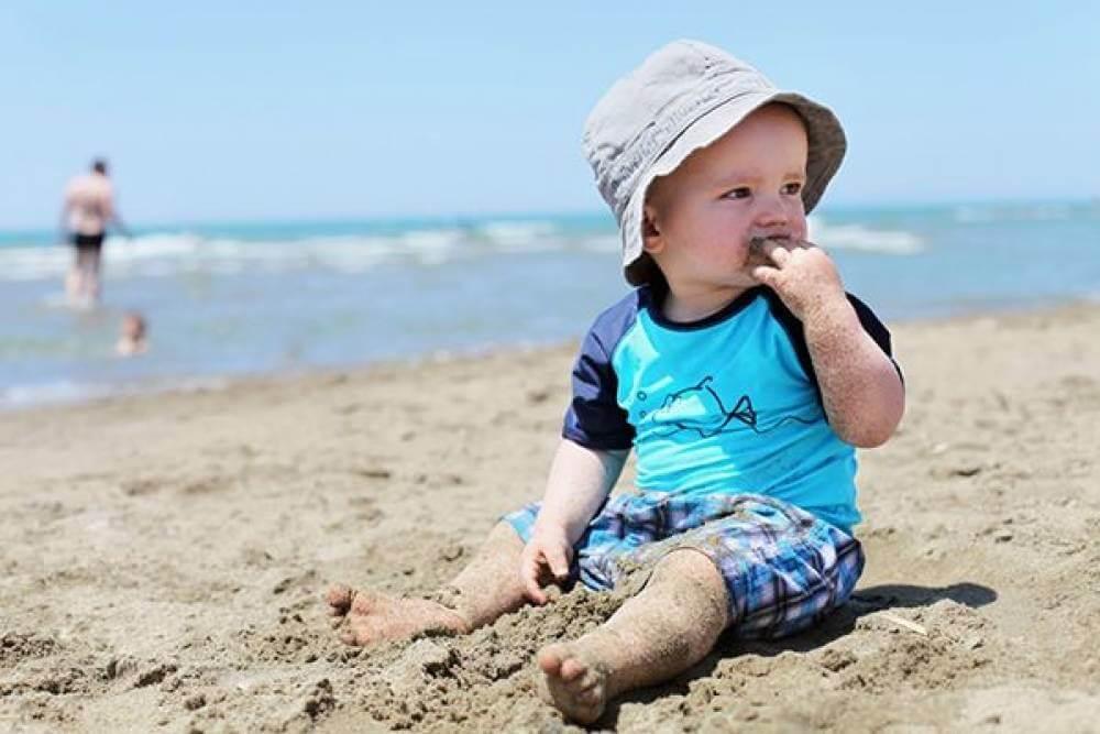 Ребенок на пляже кушает песок